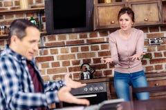 centre sélectif de l'épouse et du mari ayant l'argument dans la cuisine à la maison financière images stock