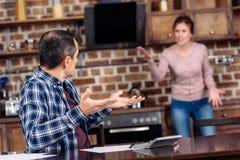 centre sélectif de l'épouse et du mari ayant l'argument dans la cuisine à la maison financière photo libre de droits