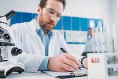 centre sélectif de scientifique dans le manteau blanc et des lunettes faisant des notes en bloc-notes sur le lieu de travail images stock