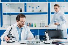 centre sélectif de scientifique dans le manteau et des lunettes blancs sur le lieu de travail avec le microscope et le collègue d photographie stock