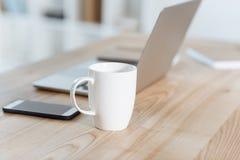 centre sélectif de tasse de café se tenant sur la table avec les dispositifs numériques image libre de droits