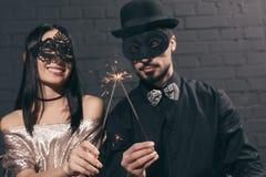 centre sélectif des couples multi-ethniques élégants dans des masques de Noël avec des étincelles à nouveau images stock