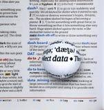 Centre-se sobre dados da palavra ampliando um globo de vidro Fotografia de Stock Royalty Free