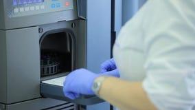 Centrifuga del laboratorio medico Uno scienziato della femmina carica le fiale di liquido in una centrifuga in un laboratorio sci archivi video