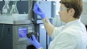 Centrifugador do laboratório médico Um cientista da fêmea carrega tubos de ensaio do líquido em um centrifugador em um laboratóri filme