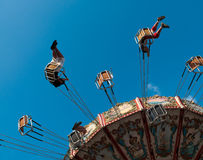 Centrifugal Force. View underneath riders thrown outwards on a swing carousel at an amusement park Royalty Free Stock Image