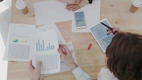 Centro analitico di vista della gente di affari sopraelevati superiori del gruppo Gli impiegati analizzano le citazioni sul cambi archivi video