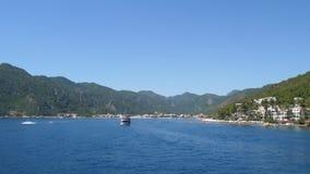 Centro balneare, nuotata del battello da diporto su chiara acqua blu contro delle montagne di estate archivi video