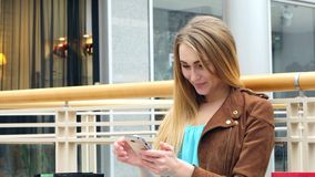 Centro comercial que se sienta de la mujer rubia con el teléfono adentro almacen de metraje de vídeo