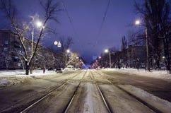 Centro da estrada nevado com trilhos A cidade da noite com tráfego da noite fotos de stock royalty free