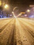 Centro da estrada nevado na cidade da noite com queda de neve fotografia de stock royalty free