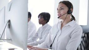Centro de atención telefónica Mujer sonriente en el funcionamiento de las auriculares en el ordenador almacen de video