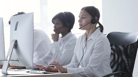Centro de atención telefónica Mujer sonriente en el funcionamiento de las auriculares en el ordenador metrajes