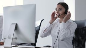Centro de atención telefónica Operador de la mujer en auriculares en ayuda de la línea directa almacen de metraje de vídeo