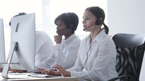 Centro de chamadas Mulher de sorriso no funcionamento dos auriculares no computador filme