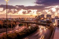 Centro de ciudad con la autopista ocupada durante puesta del sol Imagen de archivo libre de regalías