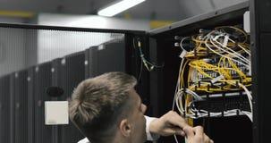 Centro de datos masculino de Walks Through Working del ingeniero del servidor por completo de servidores del estante almacen de metraje de vídeo