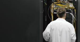Centro de datos masculino de Walks Through Working del ingeniero del servidor por completo de servidores del estante metrajes