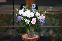 Centro de flores en colores pastel de las rosas y de las orquídeas Foto de archivo