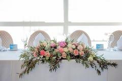 Centro de flores en la tabla Flores y mantel blanco, boda, rosas, peonías Imagen de archivo libre de regalías