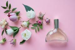 centro de flores Flores, fragancia, perfume en fondo rosado imagen de archivo