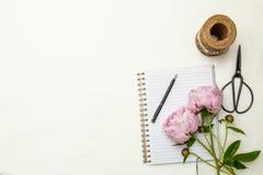 Centro de flores de las peonías con el cuaderno Imagen de archivo