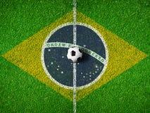 Centro de la echada o del campo del fútbol con la bandera del Brasil imagen de archivo