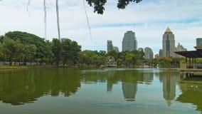Centro de negócios do prédio de escritórios que negligencia um parque verde com um lago Estilo urbano cityscape filme