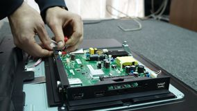 Centro de servicio Talleres de reparaciones de la electrónica El hombre está reparando la TV almacen de metraje de vídeo