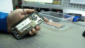Centro de servicio Talleres de reparaciones de la electrónica La reparación del smartphone Hombre que repara un smartphone metrajes