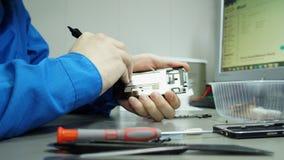 Centro de servicio Talleres de reparaciones de la electrónica La reparación del smartphone Hombre que repara un smartphone almacen de video