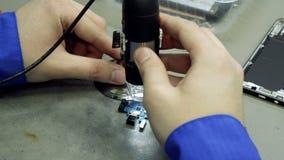 Centro de servicio Talleres de reparaciones de la electrónica La reparación del smartphone Hombre que repara un smartphone Micros almacen de video