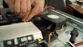 Centro de servicio Talleres de reparaciones de la electrónica Un hombre repara el avellanador multímetro almacen de metraje de vídeo
