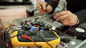 Centro de servicio Talleres de reparaciones de la electrónica Un hombre repara el avellanador multímetro almacen de video