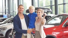 Centro de ventas del automóvil familia joven con el muchacho del niño en el coche que vende al club almacen de metraje de vídeo