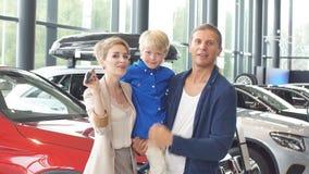 Centro de ventas del automóvil familia joven con el muchacho del niño en el coche que vende al club almacen de video