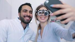 Centro dell'occhio Donna che fa foto sul telefono con il dottore On Eye Exam stock footage