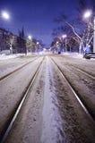 Centro della strada nevosa con le rotaie La città di notte con traffico di notte immagine stock libera da diritti