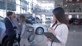 Centro di vendite dell'automobile, ritratto della femmina sorridente di Asian del responsabile sulle coppie felici dei clienti de
