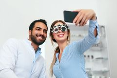 Centro do olho Mulher que faz a foto no telefone com doutor On Eye Exam imagens de stock royalty free