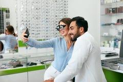 Centro do olho Mulher que faz a foto no telefone com doutor On Eye Exam foto de stock