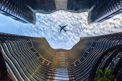 Centro finanziario moderno della metropoli con l'aereo di volo Immagini Stock