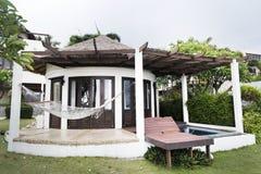 Centro turístico con el chalet de la piscina en un jardín Imágenes de archivo libres de regalías