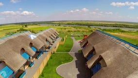 Centro turístico de lujo con las cabañas cubiertas con paja tradicionales en el delta de Danubio, aéreo almacen de video