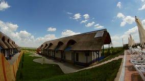 Centro turístico de lujo con las cabañas cubiertas con paja tradicionales en el delta de Danubio, lapso de tiempo metrajes