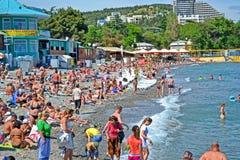Centro turístico, gente en Pebble Beach cerca del Mar Negro en Alushta, Ucrania Imagen de archivo libre de regalías