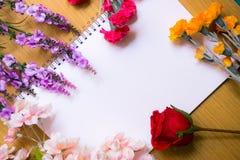 Centros de flores fresca en la página blanca del libro Fotografía de archivo