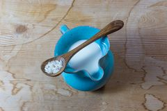 Centrowany widok mały błękitny ceramiczny miotacz ryżu mleko z drewnianą łyżką ryż na rocznika drewna stole fotografia royalty free