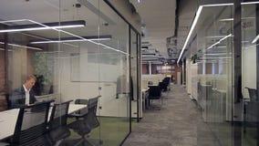 Centrum biznesu z biurami z szklanymi rozdziałami, w których pracują pracownicy zbiory wideo