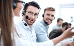 Centrum telefoniczne personel dyskutuje coś w miejsce pracy zdjęcia stock